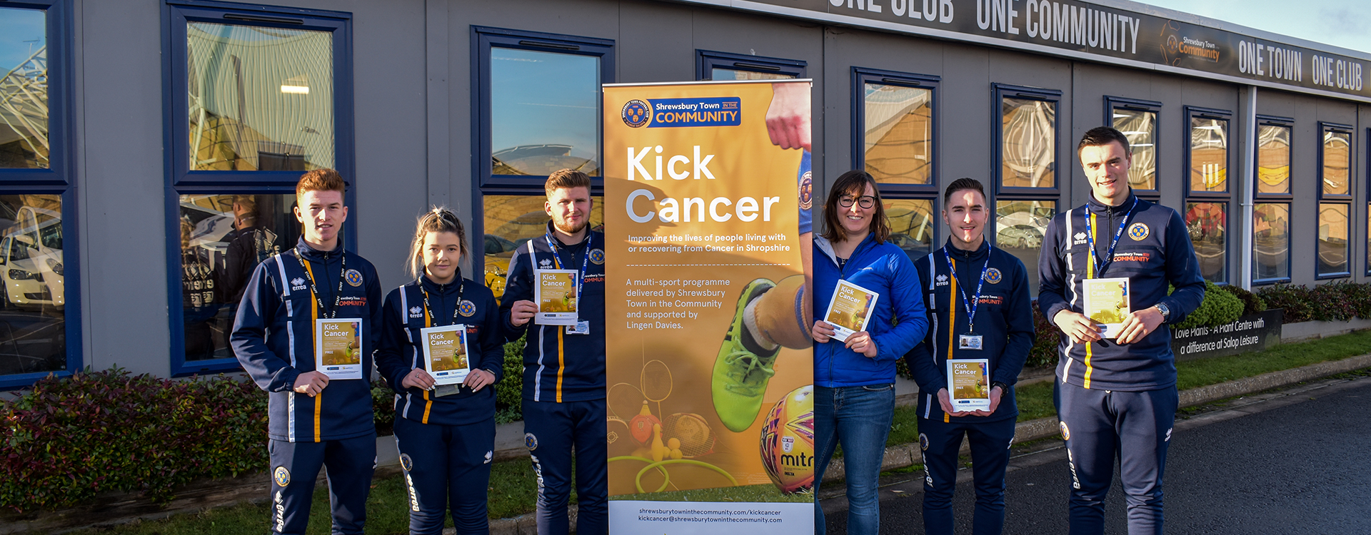 Students and Lingen Davies pose with Kick Cancer banner